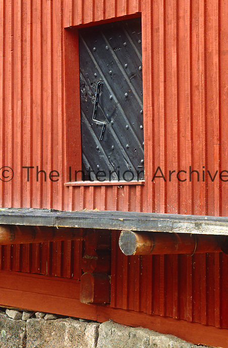 An antique studded window shutter constructed on the diagonal and painted black creates a stunning contrast to the surrounding red-painted wooden exterior of a country house in Finland