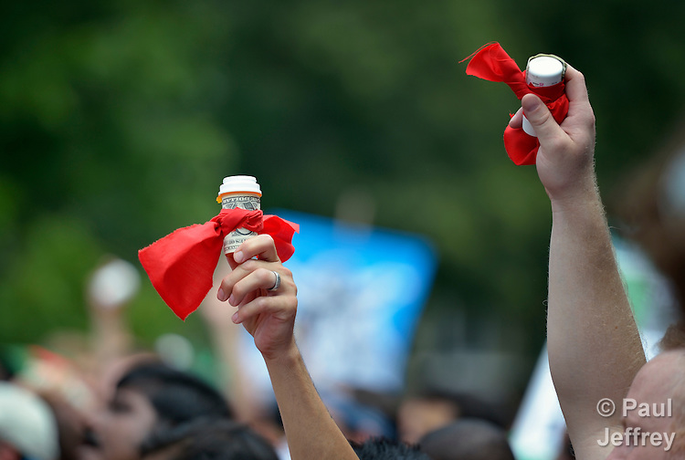 Protestors hold high prescription bottles, some wrapped in dollar bilsl, during a demonstration outside the White House on July 24, 2012, the criticized U.S. government support for pharmaceutical companies which have resisted generic licenses for their drugs for people living with HIV and AIDS. The protest took place during the XIX International AIDS Conference.