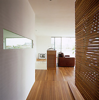 View along the iroko flooring of the penthouse between the enclosed bed and the wall of the wet room towards the living area