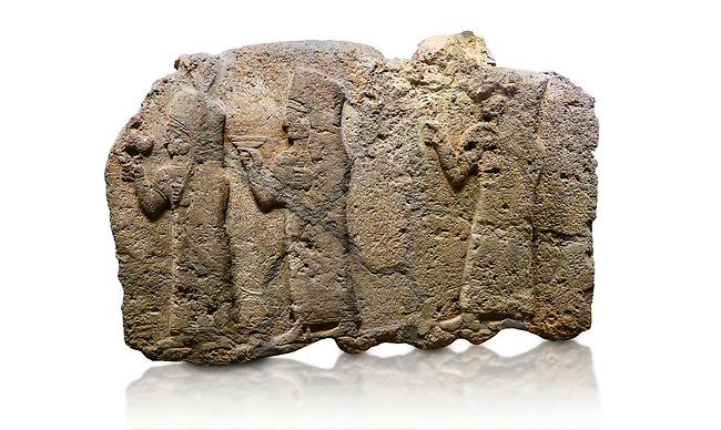 Hittite monumental relief sculpted orthostat stone panel of a Procession. Limestone, Karkamıs, (Kargamıs), Carchemish (Karkemish), 900 - 700 B.C. Anatolian Civilisations Museum, Ankara, Turkey.<br /> <br /> It is a depiction of three marching female figures in long dress with a high headdress (photos) at their head. These women are considered to be the nuns of the Goddess Kubaba. The figure in the front has a small animal in her right hand while the figure in the middle has a glass in his right hand. The object which the figures carry in their left is not understood.  <br /> <br /> Against a white background.