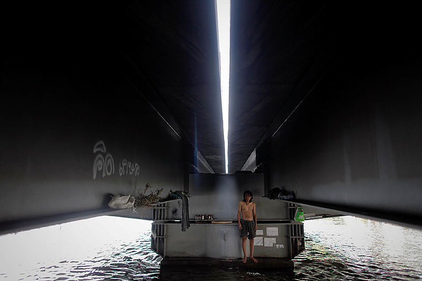 A homeless man stands under the bridge where he lives in flooded area in central Bangkok November 10, 2011. Thai consumer confidence fell to a 10-year low in October because of flooding that has taken 533 lives and shut thousands of factories, with another industrial estate threatened on Thursday as water spread in the east of the capital, Bangkok.  REUTERS/Damir Sagolj (THAILAND)