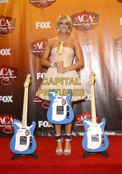 Carrie Underwood.2011 American Country Awards at the MGM Grand Resort Hotel and Casino, Las Vegas, Nevada, USA.   .December 5th, 2011.full length strapless cream beige guitars dress.CAP/ADM/MJT.© MJT/AdMedia/Capital Pictures.