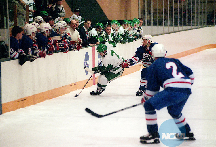 Caption: 14 MAR 1997: Bemidji State's Mike Donaghue (7) skates past the box under pressure from University of Alabama-Huntsville opponents during the Division 2 Men's Hockey Championship at Bemidji State University in Bemidji, MN. Bemidji defeated Alabama 4-2 for the championship title. Monte Draper/NCAA Photos.
