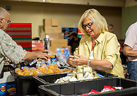 NWA Democrat-Gazette/JASON IVESTER <br /> Judy Cowan of Rogers helps separate food items on Thursday, Aug. 27, 2015, inside the Samaritan Community Center in Rogers for the Snackpacks for Kids program. The group from First United Methodist Church of Rogers volunteers monthly at the center. The program supplies food for over 7700 students in the region from headstart through high school.