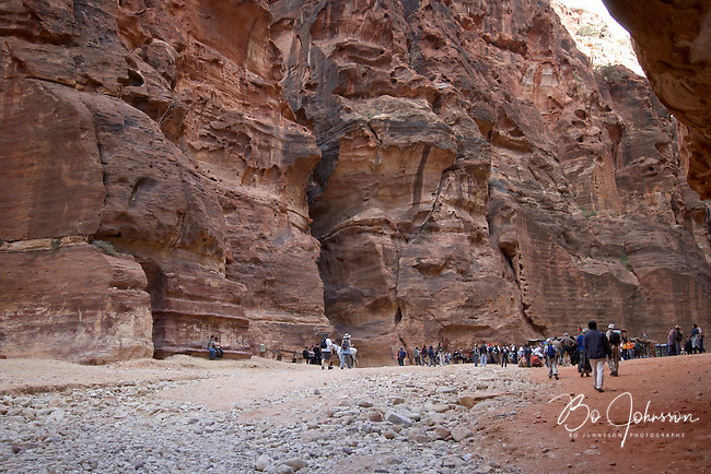 The narrow As-Siq, the lovely 1200 meter long and deep gorge is emerging in front of the huge Treasury (Al-Khazneh).<br /> After the walk in the beautiful As-Siq it's a magic moment as the huge iconic monument suddenly appear in front of you.<br /> Petra, Jordan.<br /> April 2006.<br /> Only for editorial use.