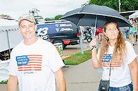 """A couple wears """"Iowans for Trump"""" shirts as they walk past the Political Soapbox on a rainy day at the Iowa State Fair in Des, Moines, Iowa, on Sun., Aug. 11, 2019."""
