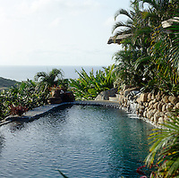 A terrace of natural stones edges this outdoor swimming pool, where a waterfall cascades into its rippled surface