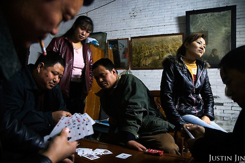 """Factory boss Mr Huang (top left corner) plays cards with fellow bosses and their wives at his home in Zhongshan city, China. .This picture is part of a photo and text story on blue jeans production in China by Justin Jin. .China, the """"factory of the world"""", is now also the major producer for blue jeans. To meet production demand, thousands of workers sweat through the night scrubbing, spraying and tearing trousers to create their rugged look. .At dawn, workers bundle the garment off to another factory for packaging and shipping around the world..The workers are among the 200 million migrant labourers criss-crossing China.looking for a better life, at the same time building their country into a.mighty industrial power."""