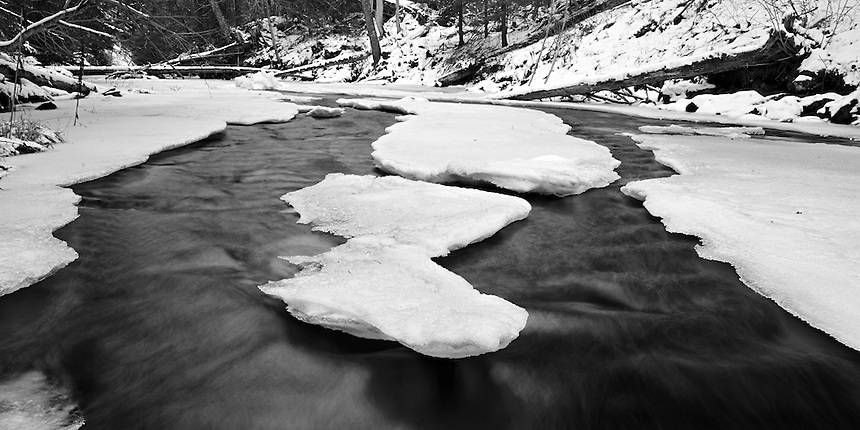 Narrowing channels of open water on the freezing Laughing Whitefish River. Alger County, Michigan's Upper Peninsula