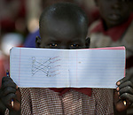 A boy displays his notebook in an outdoor classroom at the Loreto Primary School in Rumbek, South Sudan. While the school, run by the Institute for the Blessed Virgin Mary--the Loreto Sisters--of Ireland, focuses on educating girls from throughout the war-torn country, it also educates children from nearby communities. The school is building more classrooms, but in the meantime some of the children study outdoors under the trees.