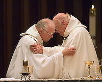 Two priests embrace during Mass at the Belmont Abbey Basilica in Belmont, NC.