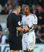 Andre Ayew of Swansea City shares a joke with referee Kevin Friend during the Barclays Premier League match between Swansea City and Arsenal played at The Liberty Stadium, Swansea on October 31st 2015