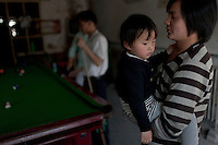 A resident carries his daughter as he visits a snooker parlour at Dawangjing Village which is being demolished on April 9, 2009 on the outskirts of Beijing, China. The local authorities are evicting residents, who are mainly migrant workers, to redevelop the area. The redevelopment of Beijing continues in high speed.