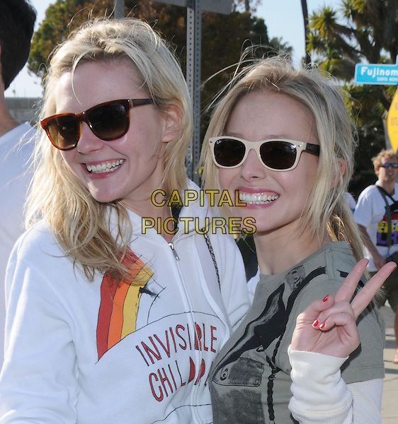 "KIRSTEN DUNST & KRISTEN BELL.City Hall at The Invisible Children's ""THE RESCUE"" Rally at City Hall in Santa Monica, California, USA, .April 25th 2009..portrait headshot green gun print t-shirt white top ray bans wayfarers sunglasses cream two tone hoodie hand waving v peace sign .CAP/DVS.©DVS/RockinExposures/Capital Pictures"