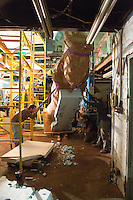 "Zach Kainz (left), Miguel Antonio Horn, and Joel Erland hoist up Horn's sculpture ""Colossus"" in HumanKind Design's studio in Germantown, October 31, 2013."