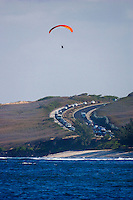 Traffic heading to St Leu, Reunion Island with a hang glider flying overhead. Photo: Joli