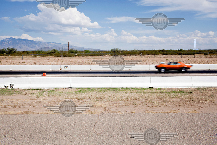 A car races the one mile strip at the Tucson Dragway where vehicles originally manufactured between the 1950s and 1980s, and now owned mainly by well off pensioners, compete against each other.