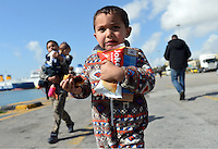 Pictured: A young carries food handouts after having just arrived to Piraeus port, Greece Sunday 28 February 2016<br /> Re: Hundreds of migrants have arrived from the Greek islands to Piraeus Port, Greece