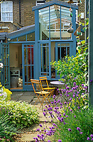 A double-height conservatory has a flag-stone patio beyond the French windows for outdoor dining
