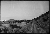 View of railroad grade at Otowi bridge crossing Black Mesa in background.<br /> D&amp;RGW  Otowi, NM