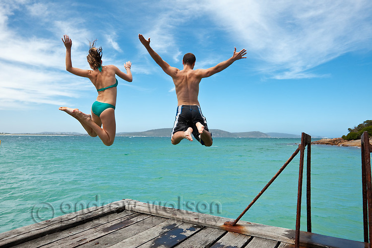 Couple leaping off a jetty.  Middleton Beach, Albany, Western Australia, Australia