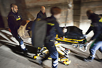 Switzerland. Canton Ticino. Sonvico. A woman lying down on an emergency medical stretcher is being transported from home. The woman is suffering from a stroke and needs to be brought urgently to the hospital for medical examinations. At night time on a narrow street, four paramedics are pushing the stretcher to the ambulance. The paramedics wear blue uniforms and work for the Croce Verde Lugano. The man (R) and the woman (center right) are professional certified nurses, the two others are volunteers specifically trained in emergency rescue. The Croce Verde Lugano is a private organization which ensure health safety by addressing different emergencies services and rescue services. Volunteering is generally considered an altruistic activity where an individual provides services for no financial or social gain to benefit another person, group or organization. Volunteering is also renowned for skill development and is often intended to promote goodness or to improve human quality of life. 20.01.2018 © 2018 Didier Ruef
