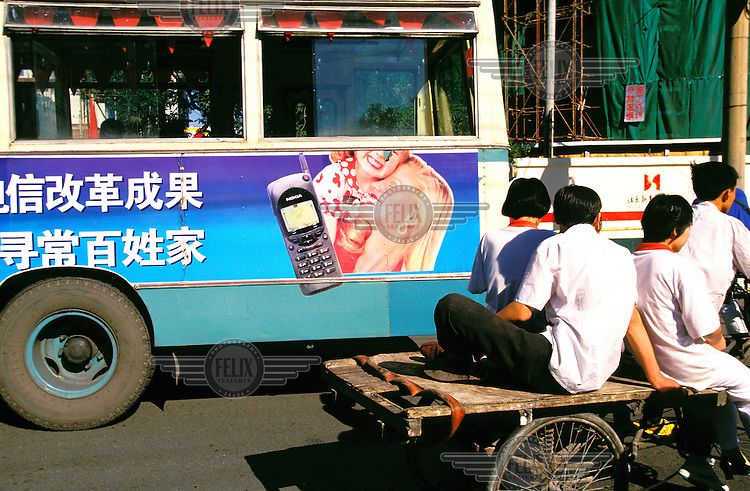 Mark Henley/Panos Pictures..China, Beijing..Contrast - people on back of cart next to bus carrying advertising for mobile phone using western blond woman and child models.