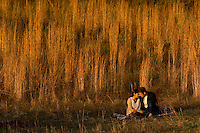 A couple basks in the glow of a setting sun while relaxing near a Carolina field. (Have model releases).