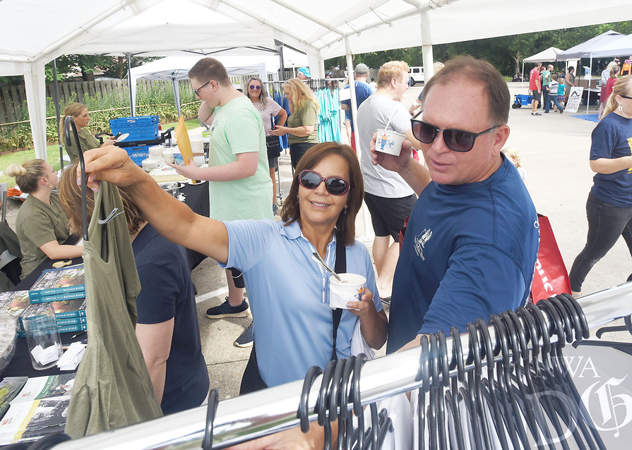 NWA Democrat-Gazette/FLIP PUTTHOFF <br /> HONORING DR. COMPTON<br /> Isabel Rodriguez (cq) and Jeff Montgomery, both of Springdale, enjoy free ice cream while buying souvenir shirts on  Satuday Aug. 10 2019 during Dr. Compton Day at Compton Gardens in downtown Bentonville. The annual event honors the late Dr. Neil Compton, a Bentonville physician. He was a founder of the Ozark Society which was instrumental in keeping the Buffalo National River free of dams. Dr. Compton championed  conservation efforts in Arkansas and beyond. The aluminum canoe he paddled is on display at Compton Gardens, two blocks north of the town square.