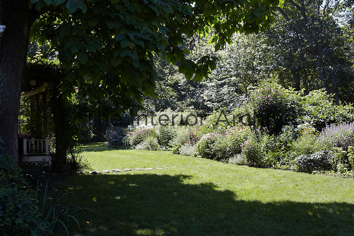 The sunlit lawn is bordered by flowerbeds filled with plants