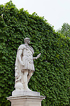 Marble statue of Julius Ceasar against a wall of foliage in the Tuileries Gardens of Paris, France
