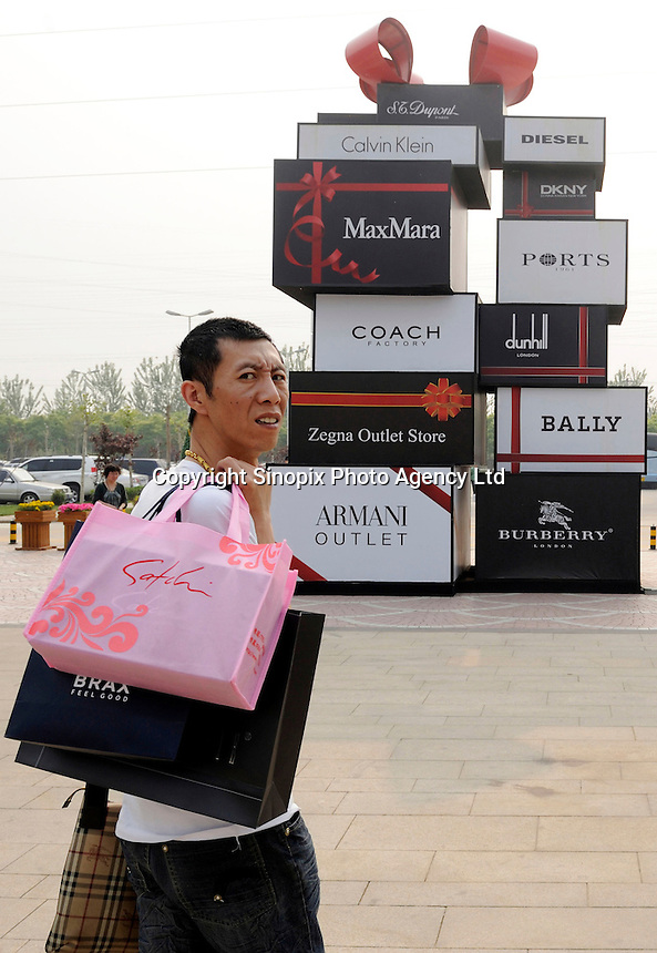 Chinese man carrying shopping bags past luxury brands bill board at Beijing Scitech Premium Outlet Mall Beijing, China. Opened in July 2009, Beijing Scitech Premium Outlet Mall is located in Beijing's most prestigious villa neighborhood. The outlet, featuring Colonial and Victorian architecture, the first of its kind in China, contains gallery of top-tier luxury brands, as well as showcases a wide selection of popular sports and leisure brands at discounted prices..15 May 2010