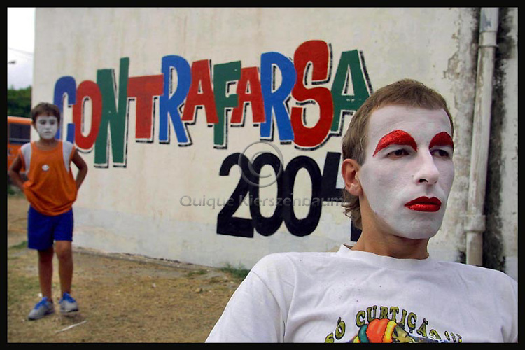 """A boy with make up in his face looks at Gerardo """"Batata"""" Canepa as he waits for someone to finish his make up during the last preparations for the inaugural parade of the Uruguayan Carnival, January 30, 2004. Murga is a dynamic form of music-theatre composed of poetry, narration, singing, music and commedia dell'arte. ..Their shows, which combine song, drama, and comedy, satirize the main events of the year and are critical of Uruguayan politics, reality and culture. .."""