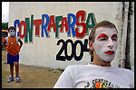 "A boy with make up in his face looks at Gerardo ""Batata"" Canepa as he waits for someone to finish his make up during the last preparations for the inaugural parade of the Uruguayan Carnival, January 30, 2004. Murga is a dynamic form of music-theatre composed of poetry, narration, singing, music and commedia dell'arte. ..Their shows, which combine song, drama, and comedy, satirize the main events of the year and are critical of Uruguayan politics, reality and culture. .."