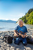 CANADA, Vancouver, British Columbia, portrait of a musician with his guitar at Wreck Beach