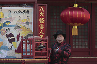 """A Chinese artist dressed in traditional costume sings to illustrate stories being displayed at a traditional mobile """"theatre"""" at a temple fair to celebrate the Lunar New Year of the Tiger on February 15, 2010 in Beijing, China."""