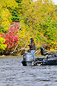 00416-032.02 Fishing: Anglers in bass boat fish along secluded shoreline during fall.  Fall color, river, lake.