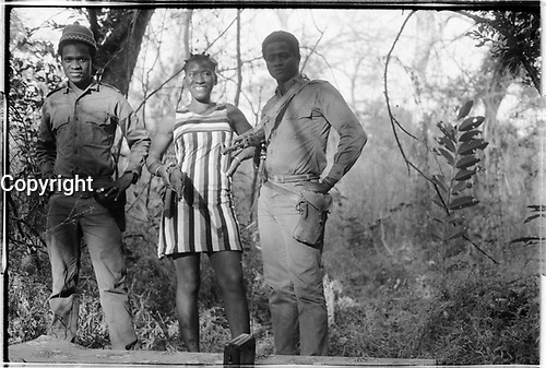 PAIGC Campada college, northern frontline. Two men and a woman posing with pistol and machine guns. Transistor radio. Striped dresse, Guinea-Bissau - Fall 1973