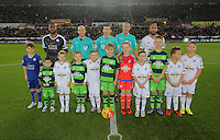 Children mascots with referee Michael Oliver and team captains Wes Morgan of Leicester City and Ashley Williams of Swansea  before the Barclays Premier League match between Swansea City and Leicester City at the Liberty Stadium, Swansea on December 05 2015