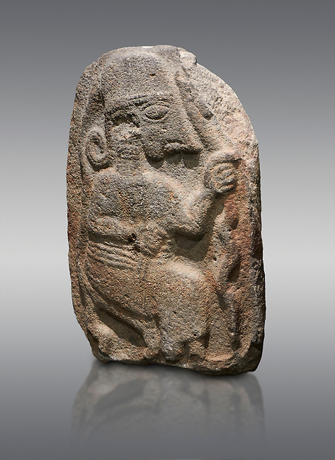 Hittite monumental relief sculpture of a seated figure. Late Hittite Period - 900-700 BC. Adana Archaeology Museum, Turkey. Against a grey background