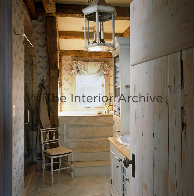 The bath is raised and the steps and bath surround painted in a grey trompe l'oeil in this rustic bathroom