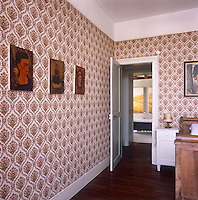 A detail of a bedroom with a bold floral pattern wallpaper. Images of the artist Freda Kahlo hang on the wall.