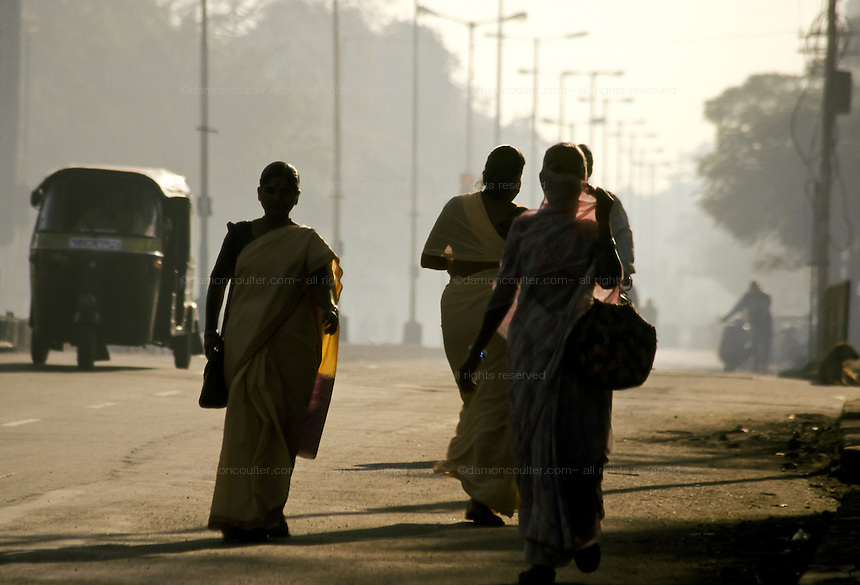 Women in sari walking along an Indian street with a Bajaj motor Rickshaw behind them. Pune, India. November 1999