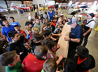 NWA Democrat-Gazette/ANDY SHUPE<br /> Volunteer interpreter Jeff Gates holds a section of a wing Tuesday, May 14, 2019, as students from Lowell Elementary School touch it as they tour the Arkansas Air and Military Museum in Fayetteville. The students spent the morning learning about flight and the history of aviation in Northwest Arkansas.