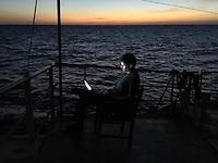 Sea Watch-2.<br /> Die Sea Watch-2 ist zu ihrer 13. SAR-Mission vor der libyschen Kueste.<br /> Im Bild: Ein Crewmitglied sitzt bei Sonnenuntergang auf dem Brueckendeck am Laptop.<br /> 19.10.2016, Mediterranean Sea<br /> Copyright: Christian-Ditsch.de<br /> [Inhaltsveraendernde Manipulation des Fotos nur nach ausdruecklicher Genehmigung des Fotografen. Vereinbarungen ueber Abtretung von Persoenlichkeitsrechten/Model Release der abgebildeten Person/Personen liegen nicht vor. NO MODEL RELEASE! Nur fuer Redaktionelle Zwecke. Don't publish without copyright Christian-Ditsch.de, Veroeffentlichung nur mit Fotografennennung, sowie gegen Honorar, MwSt. und Beleg. Konto: I N G - D i B a, IBAN DE58500105175400192269, BIC INGDDEFFXXX, Kontakt: post@christian-ditsch.de<br /> Bei der Bearbeitung der Dateiinformationen darf die Urheberkennzeichnung in den EXIF- und  IPTC-Daten nicht entfernt werden, diese sind in digitalen Medien nach §95c UrhG rechtlich geschuetzt. Der Urhebervermerk wird gemaess §13 UrhG verlangt.]