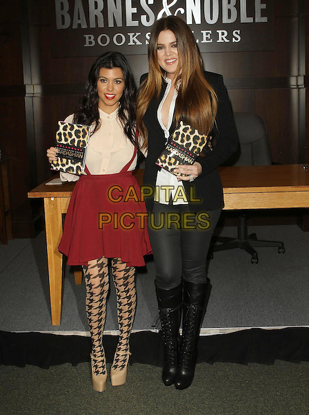 Kourtney Kardashian & Khloe Kardashioan Odom.'Dollhouse' Book signing held At Barnes & Noble at The Grove at Farmers Market, Los Angeles, California, USA, .18th November 2011..full length red pink skirt pinafore braces  beige white blouse shirt houndstooth patterned tights black beige mary janes shoes platform christian louboutin lace-up boots black jacket white shirt jeans sisters siblings .CAP/ADM/KB.©Kevan Brooks/AdMedia/Capital Pictures.