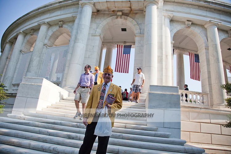 A veteran passes out American flags to visitors at the Arlington National Cemetery Memorial Amphitheater in Virginia on Memorial Day 2010.