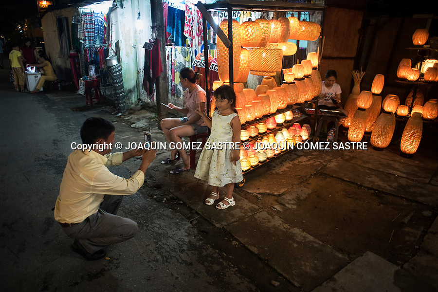 A father makes a portrait of his daughter at the night market in Hoian (Vietnam)<br /> HOIAN-VIETNAM