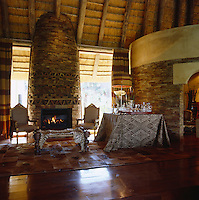 A stone-clad fireplace dominates this area of the living room where a table covered in a local textile is laden with a tray of drinks