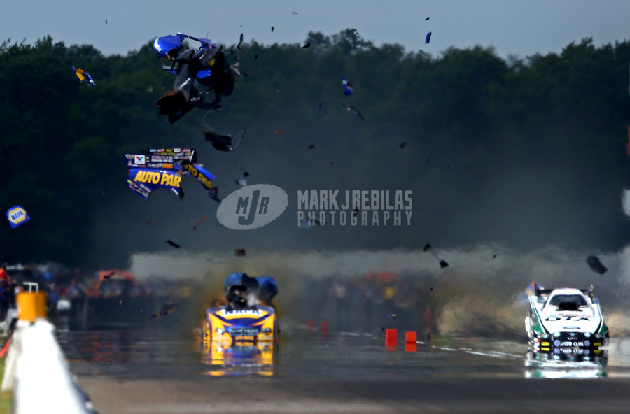 Aug. 17, 2013; Brainerd, MN, USA: NHRA funny car driver Ron Capps (left) explodes an engine shredding the carbon fiber body off his car alongside John Force during qualifying for the Lucas Oil Nationals at Brainerd International Raceway. Capps was uninjured in the explosion. Mandatory Credit: Mark J. Rebilas-